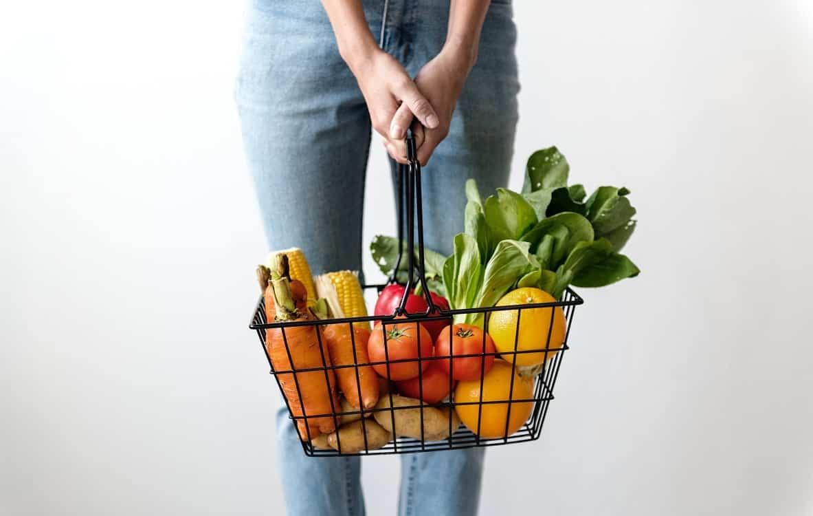 אישה מחזיקה סל קניות עם פירות וירקות