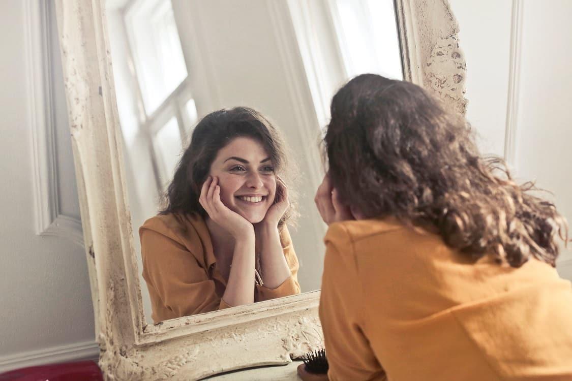 אישה צעירה מביטה במראה ומחייכת