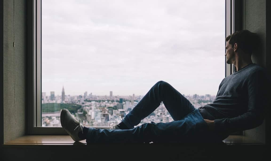 גבר יושב ליד החלון ומסיק מסקנות על צלקת אחרי השתלת שיער