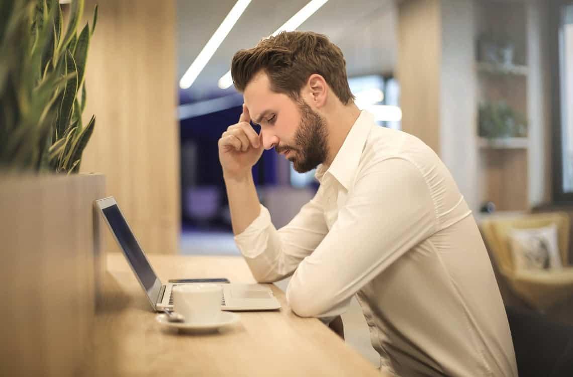 גבר מסתכל על מחשב ומחפש דרכים של טיפול צלקת אחרי השתלת שיער