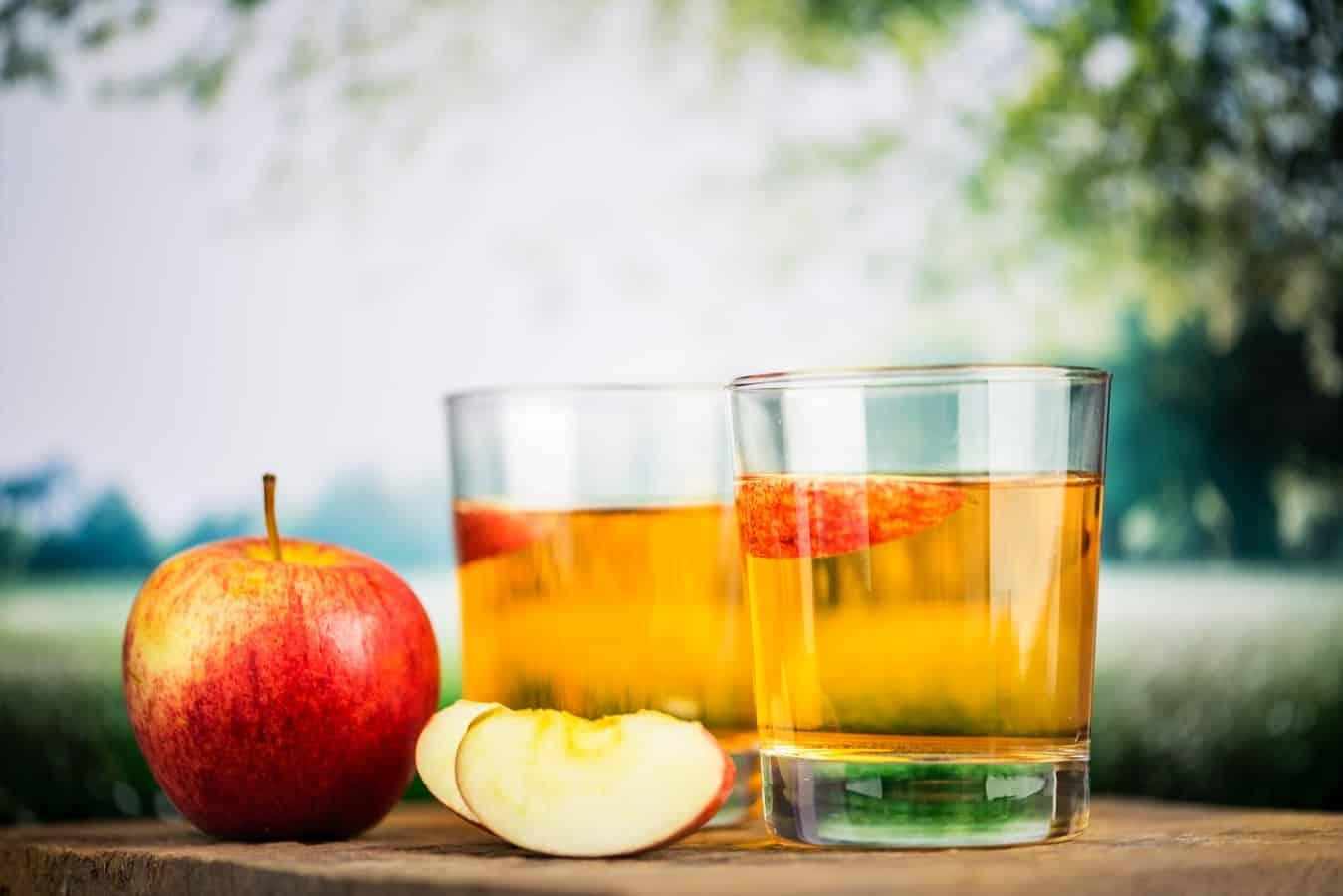 כוסות עם סיידר תפוחים על שולחן בטבע