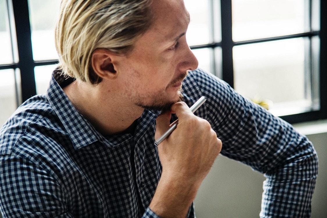קלואוז אפ של גבר חושב עם עט ביד