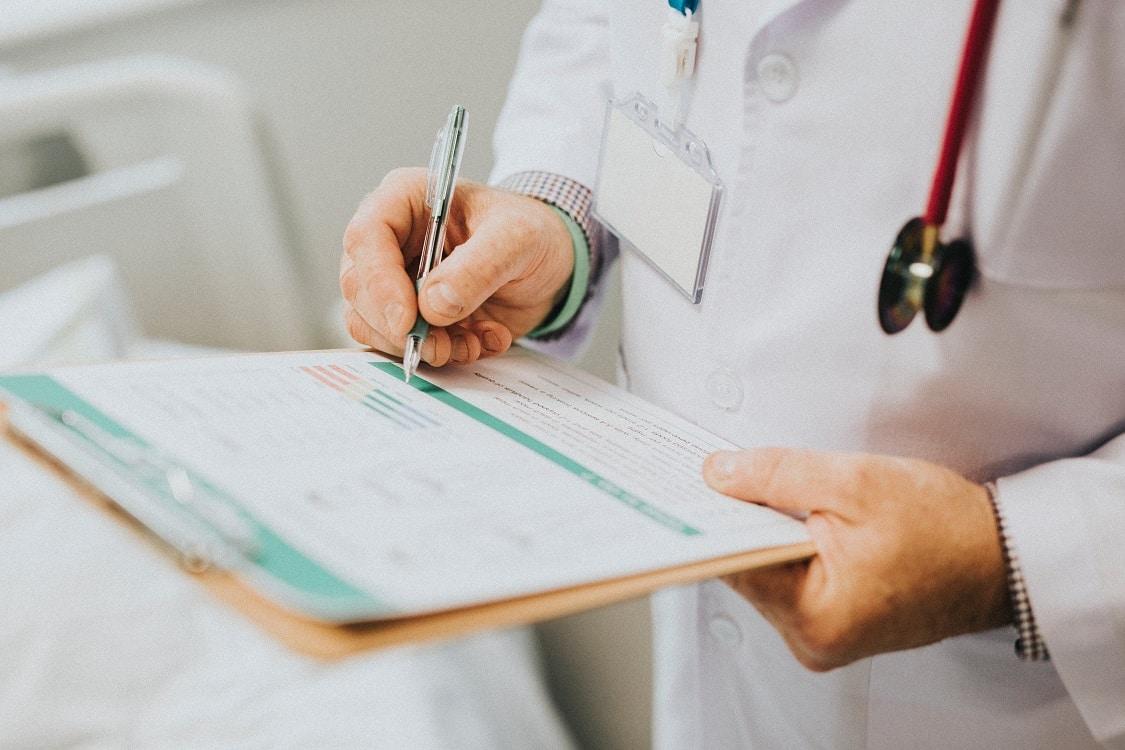 רופא עם חלוק שמסביר על אפשרויות לטיפול בנשירת שיער