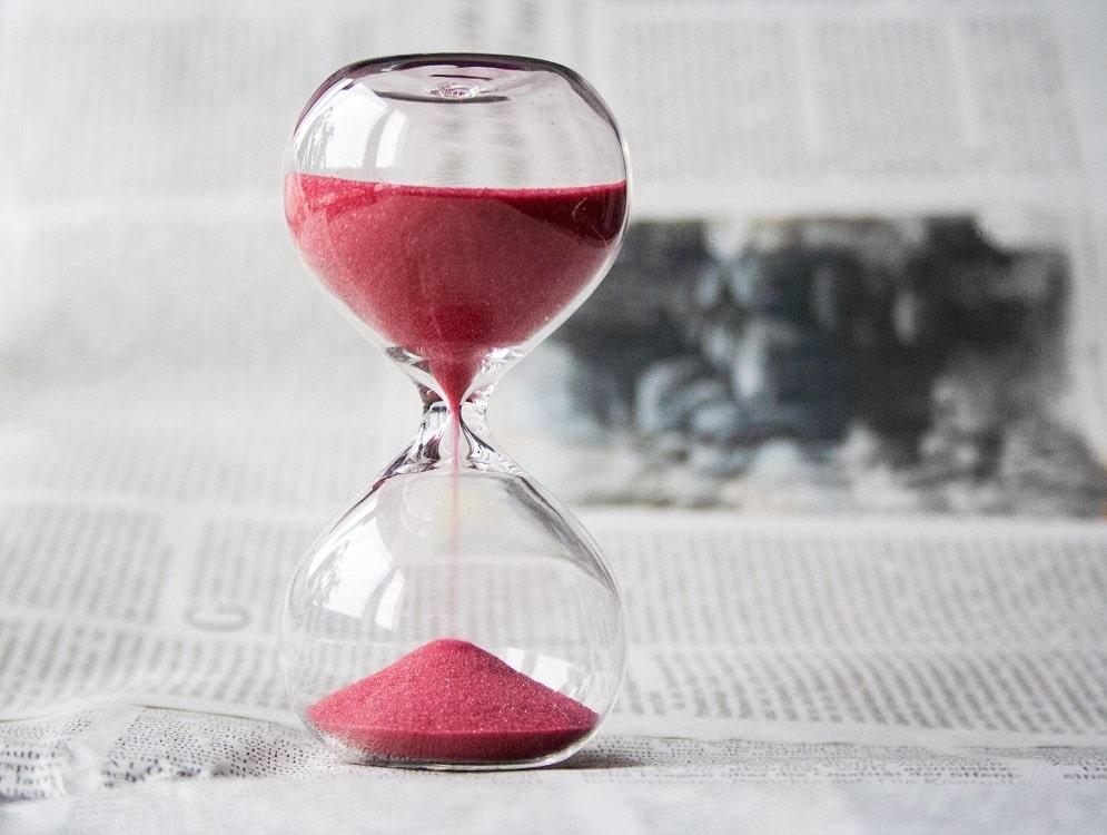 שעון חול עם חול אדום על עיתון