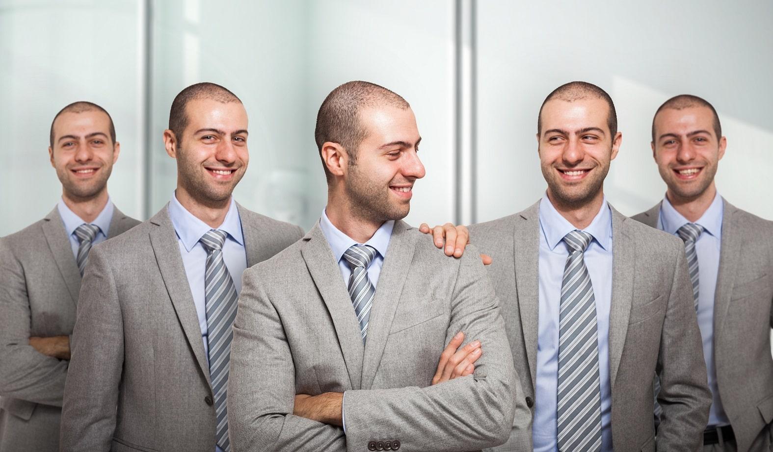 תמונה של גבר צעיר בחליפה שסובל מנשירת שיער ששיכפל את עצמו