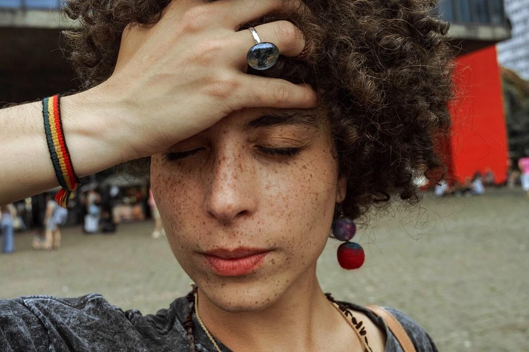אישה שסובלת מתופעות לוואי מחזיקה את הראש עם היד