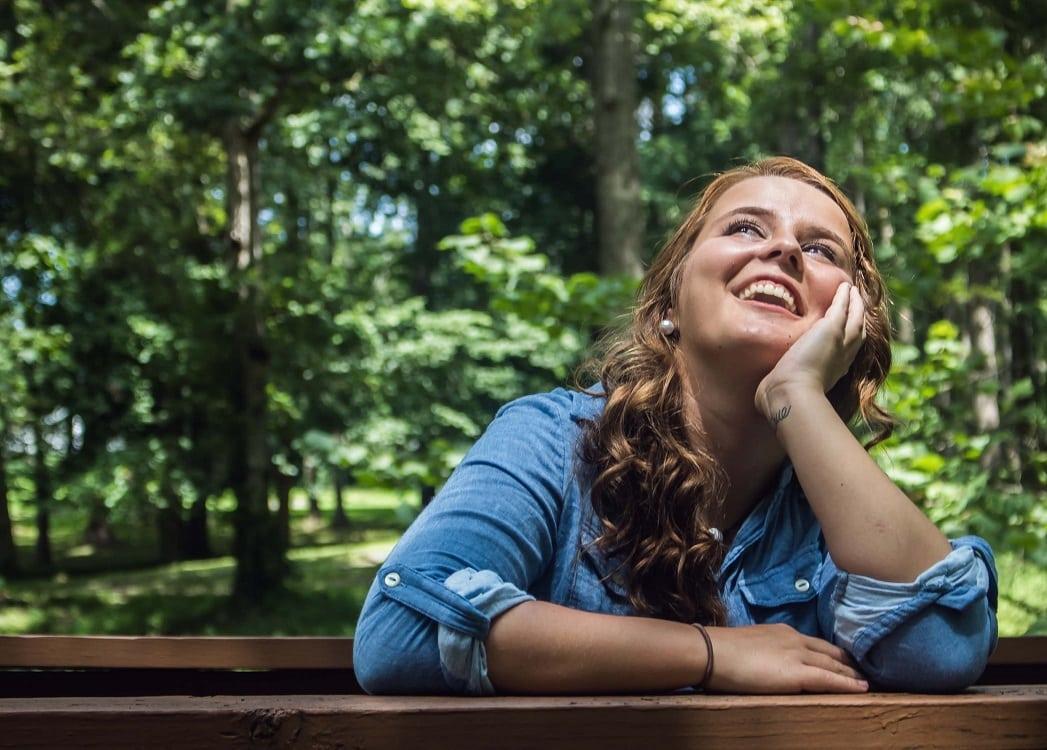 בחורה צעירה חושבת ומחייכת על רקע של עצים ירוקים