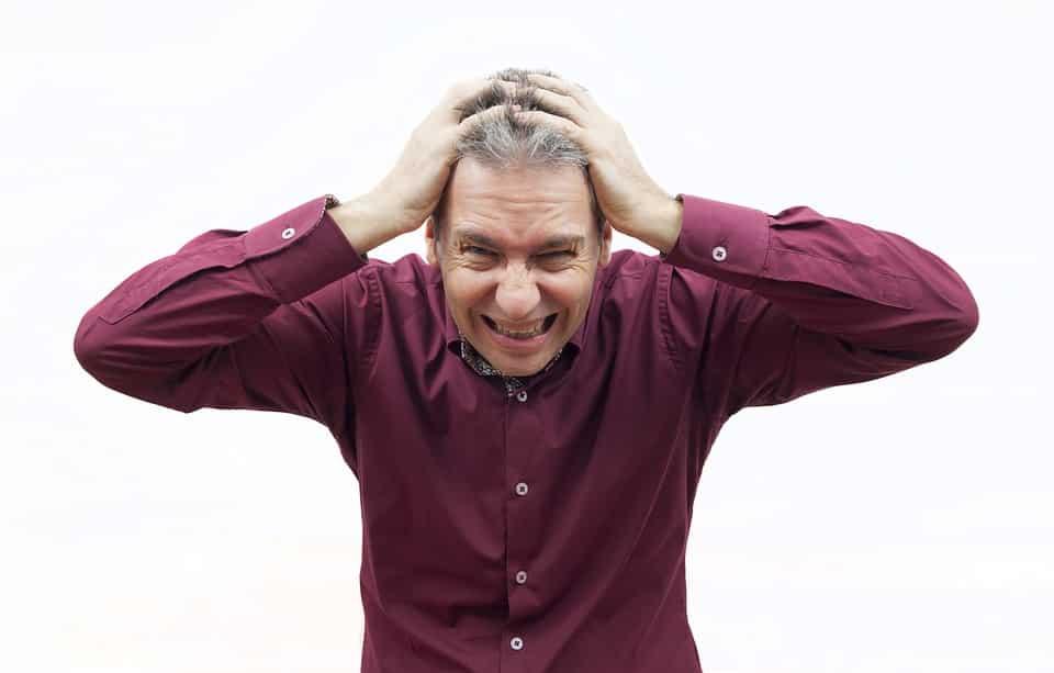 גבר בחולצה בורדו מחזיק את הראש עם הידיים ומדמה לחץ נפשי