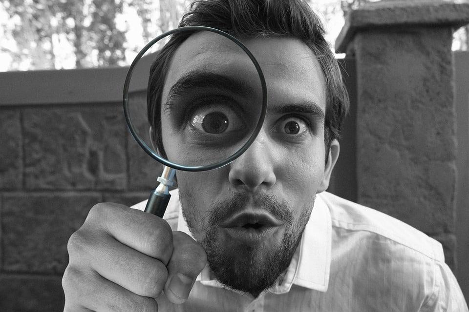 גבר עם זכוכית מגדלת מגלה סימנים מוקדמים של נשירת שיער בגיל ההתבגרות