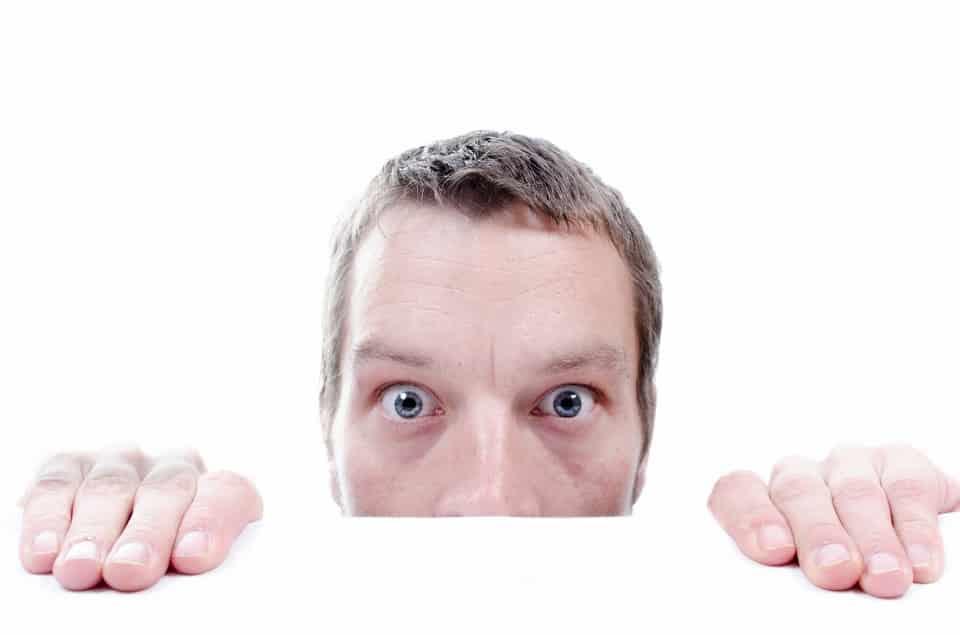 גבר עם שיער קצר ועיניים כחולות מתחבא מחאורי משהו