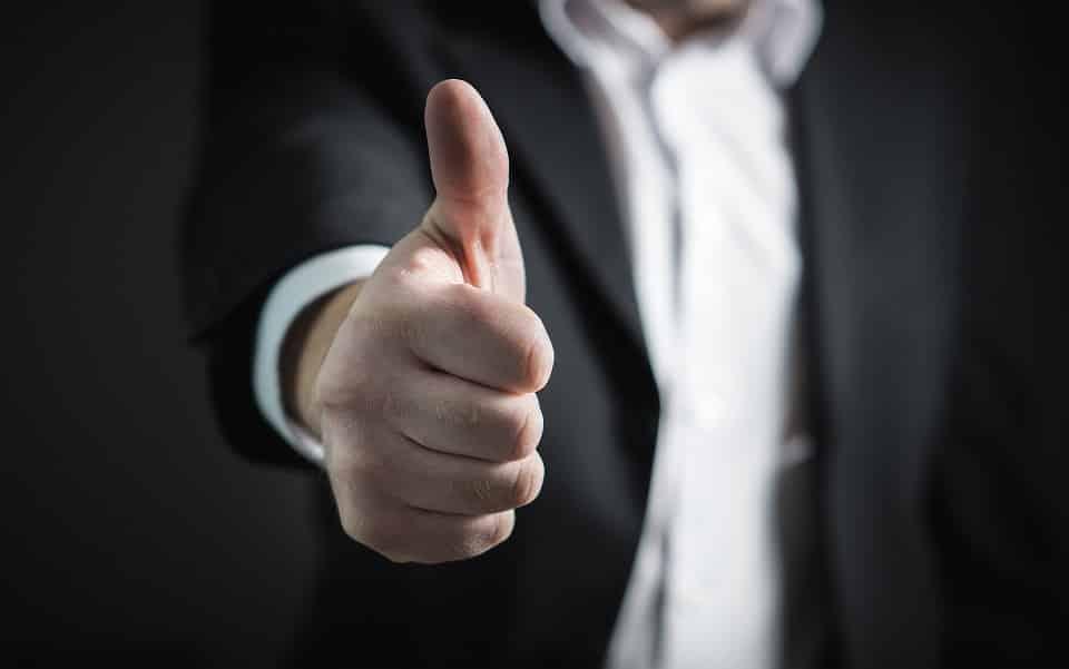 תמונה של גבר בחליפה עושה סימן עם הבוהן שהכל מצויין