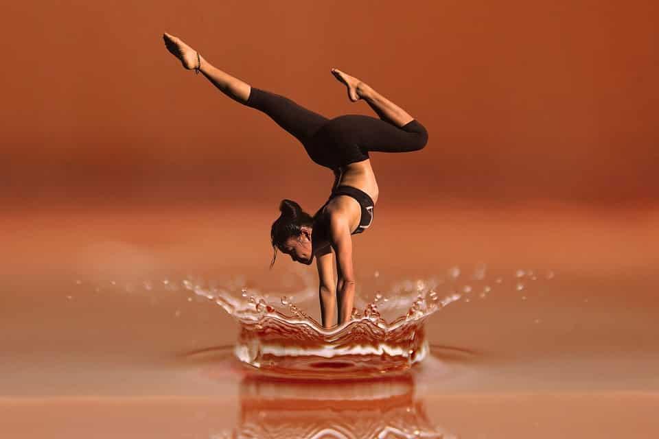 אישה אסייתית עושה עמידת ידיים במים