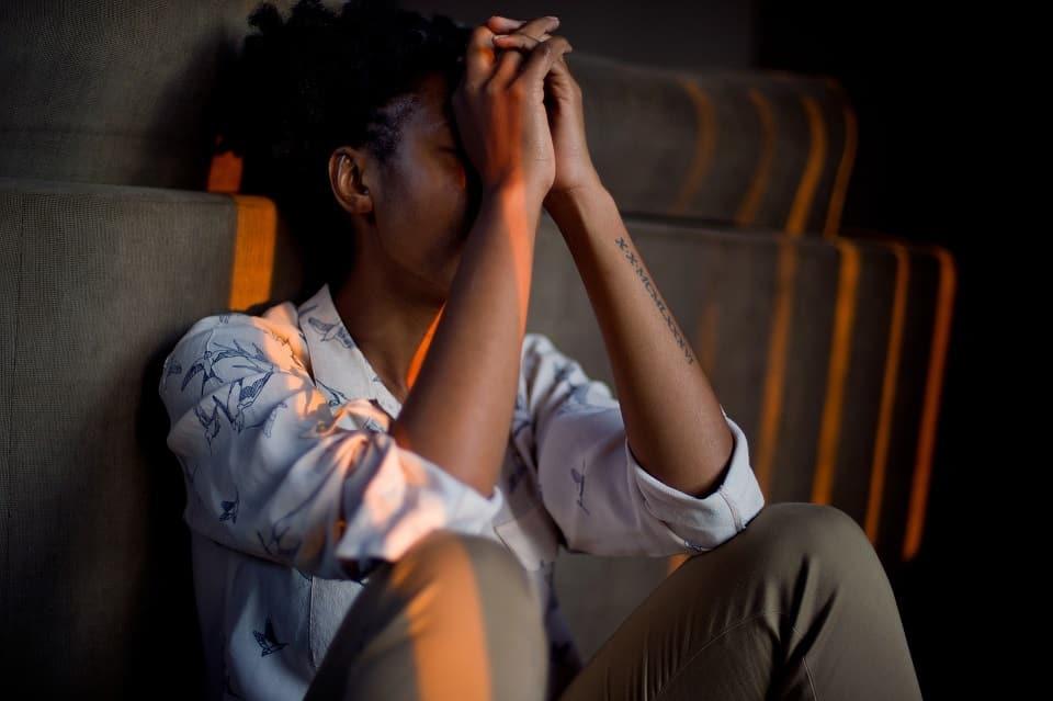 אישה המצויה תחת לחץ נפשי יושבת על הרצפה
