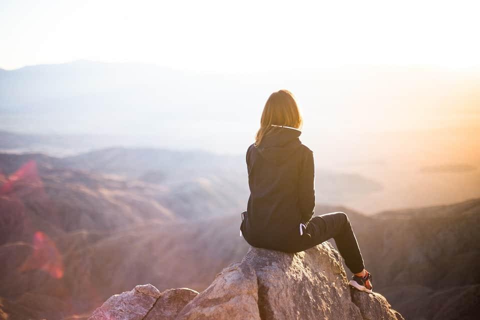 אישה יושבת על פסגה של הר ומגיעה למסקנות על עיסוי לקרקפת