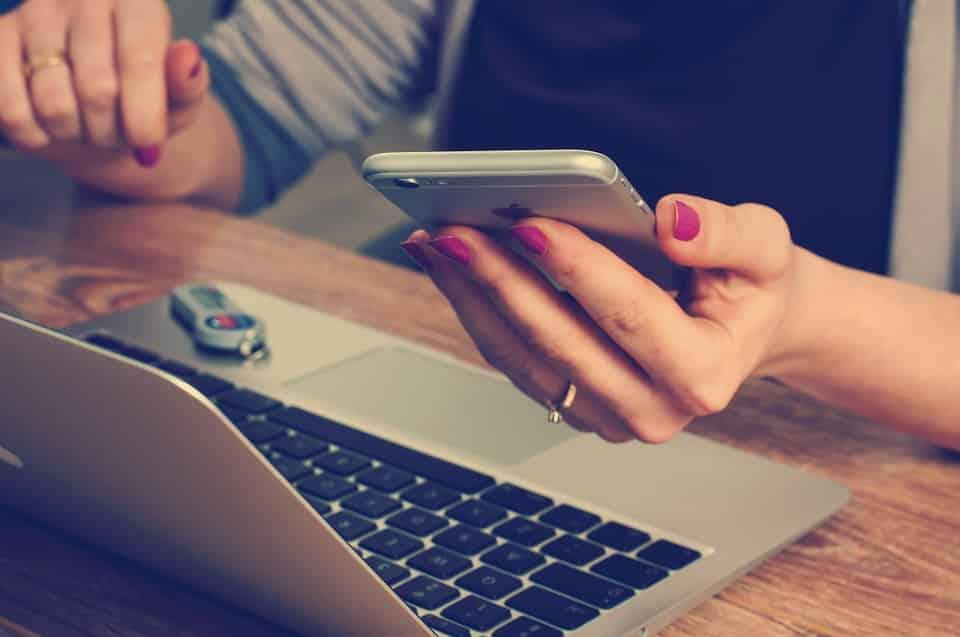 אישה מחזיקה אייפון וקוראת על חוסמי DHT טבעיים