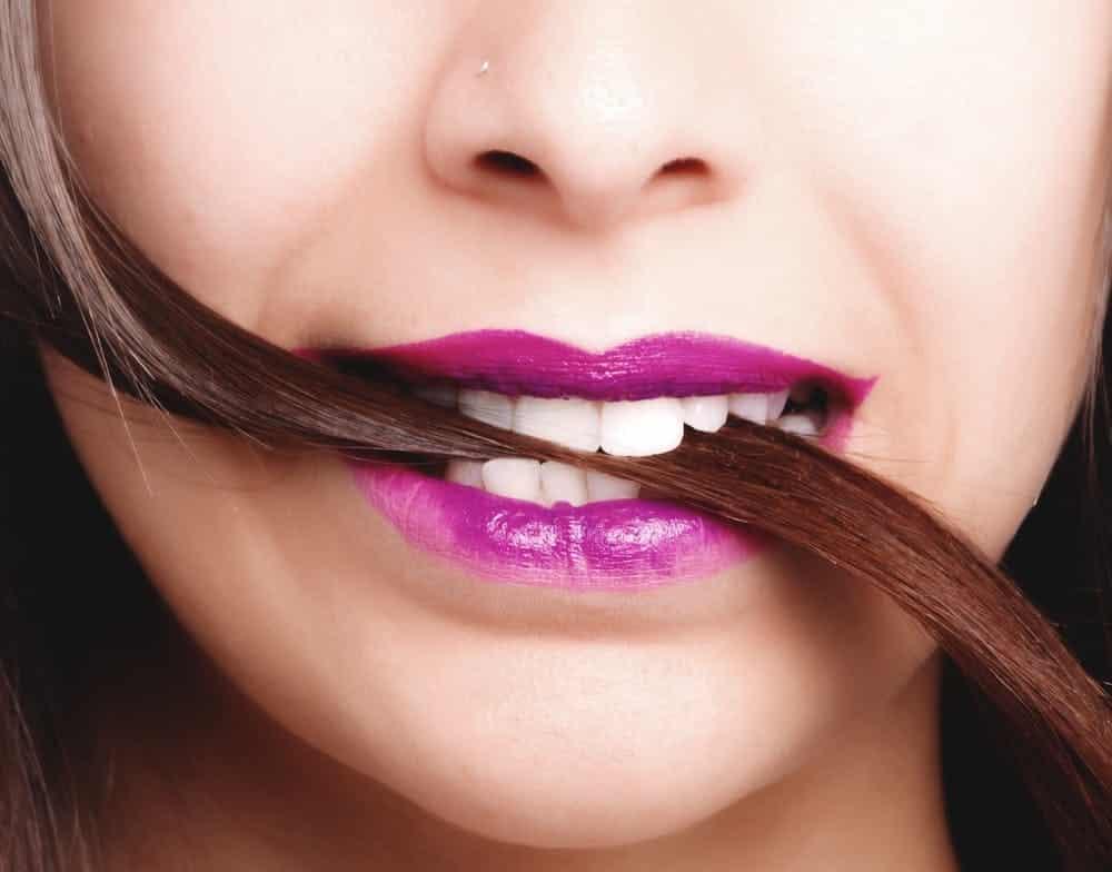 אישה מחזיקה את השיער שלה בפה בין השיניים