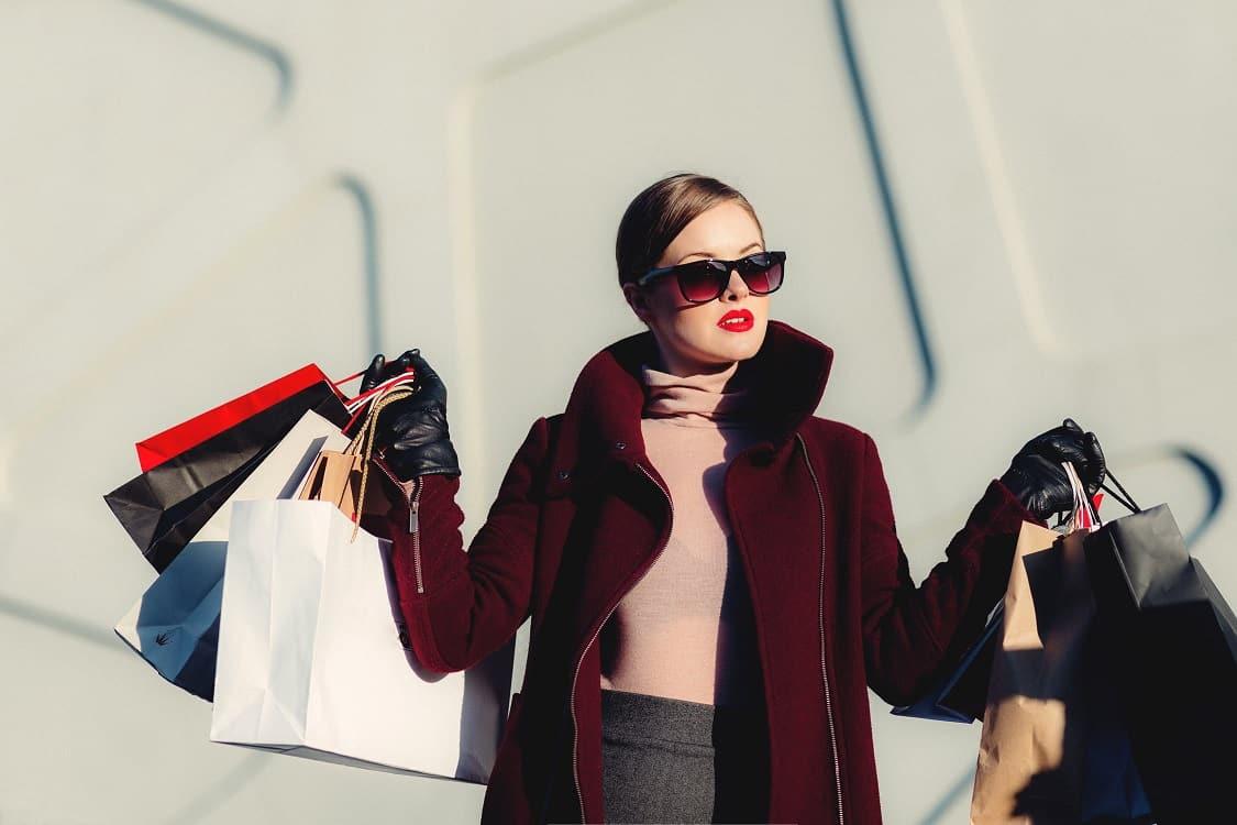 אישה מחזיקה תיקים מלאים במוצרים אחרי מסע קניות