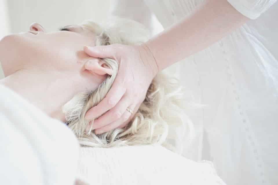 אישה עם שיער בלונדיני עוברת עיסוי ותרגילים לקרקפת
