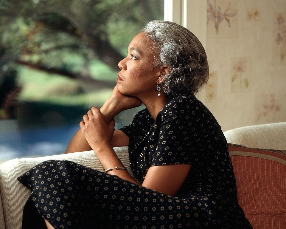 אישה פנסיונרית מסתכלת החוצה מהחלון ומגיעה למסקנות