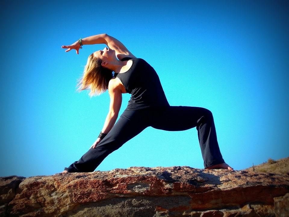 אישה צעירה מבצעת את תנוחת הלוחם כחלק מאימון יוגה