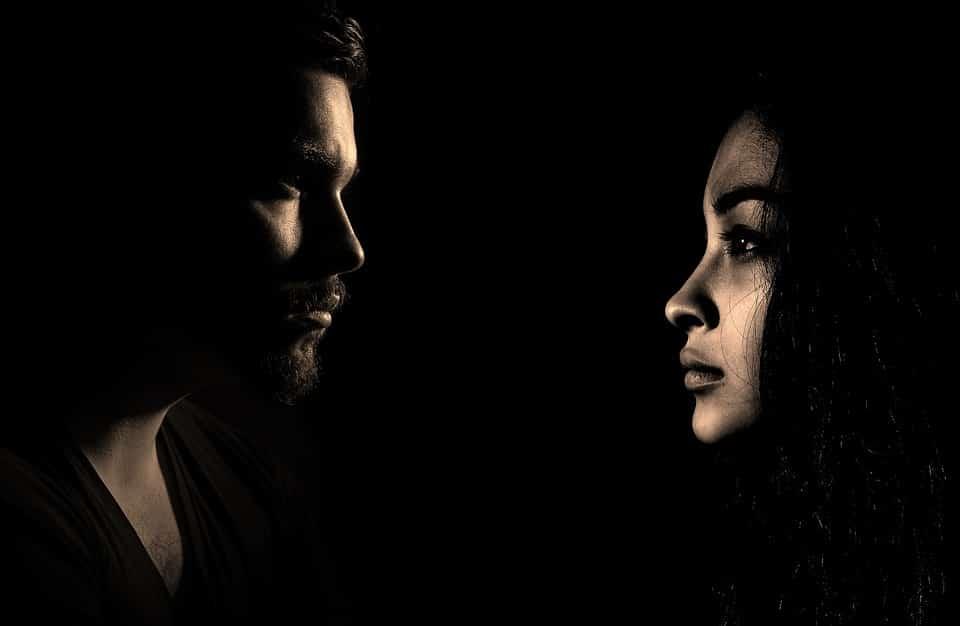 גבר ואישה מסתכלים אחד על השני בתאורה חשוכה