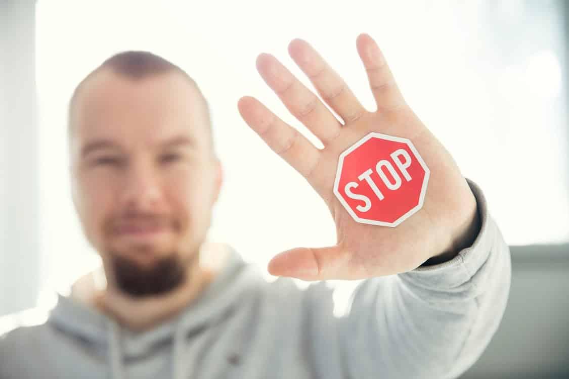 גבר עם סימן של עצור מודבק ליד שמאל