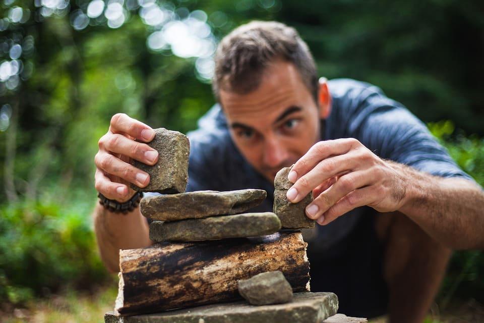גבר צעיר בונה מבנה מאבנים ועצים ביער