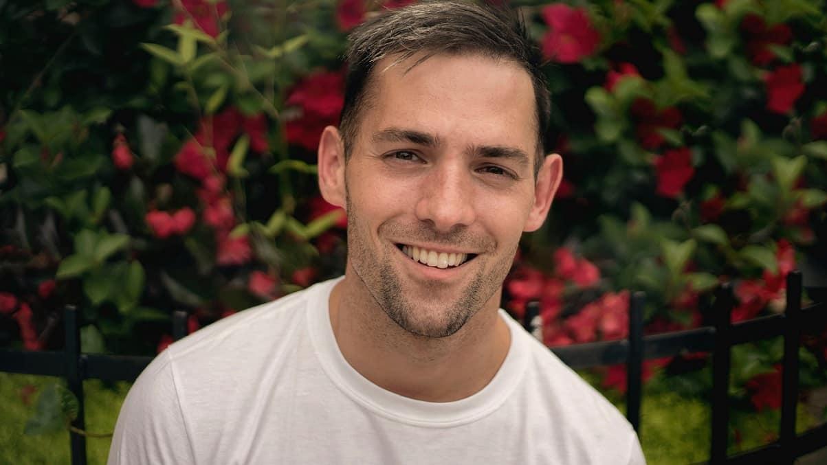 גבר צעיר מחייך על רקע של פרחים אדומים