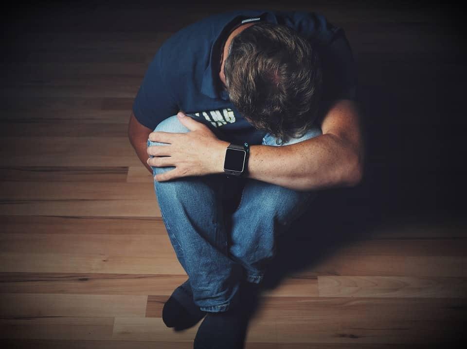 גבר שיושב על הרצפה עם הראש בין הרגליים ומדמה תופעות לוואי