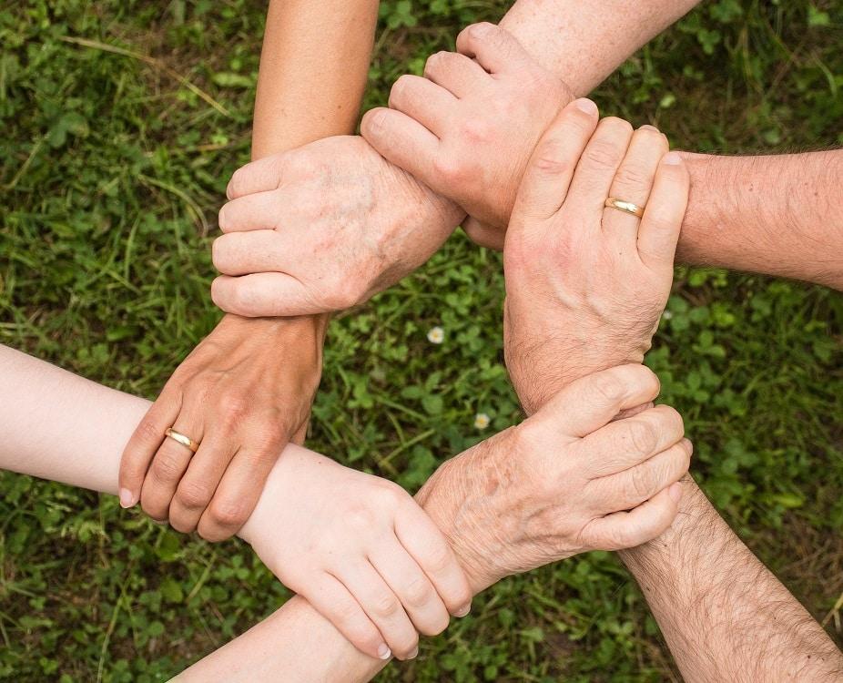 ידיים של אנשים שונים משולבות בעיגול