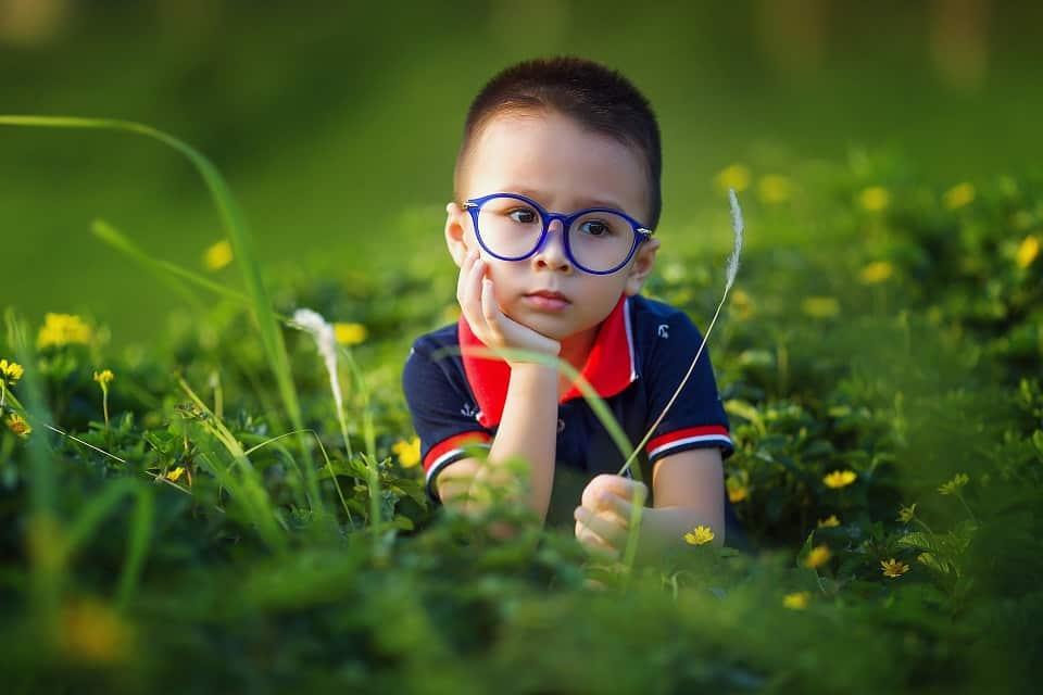 ילד שוכב על הדשא ומגיע למסקנות על תהליך השתלת שיער