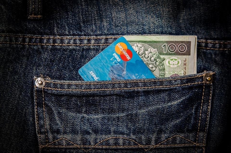 כרטיס אשראי וכסף מזומן בתוך כיס אחורי של ג'ינס