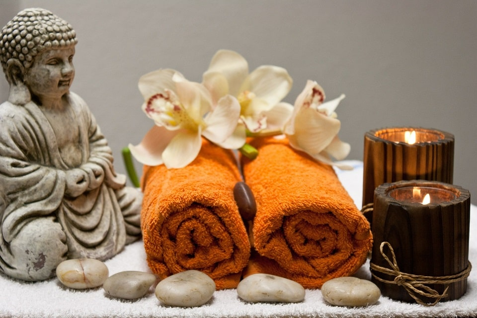 פסל בודהה עם אבנים טיפוליות מגבות ונרות ריחניים
