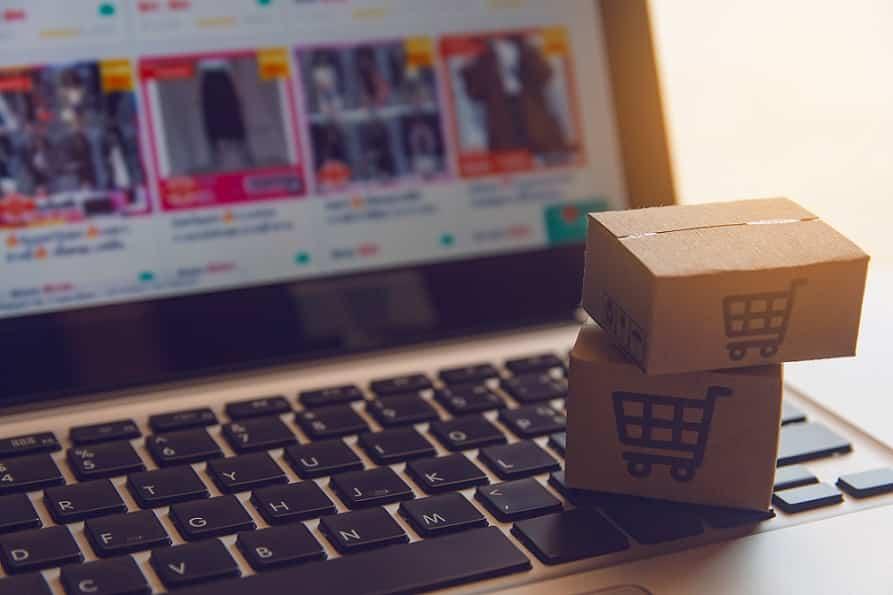 קופסאות קטנות של קניות מונחות מול מחשב