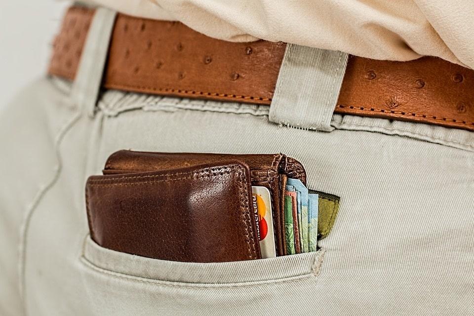 תמונה של כיס אחורי במכנסיים שיוצא ממנו ארנק עם שטרות
