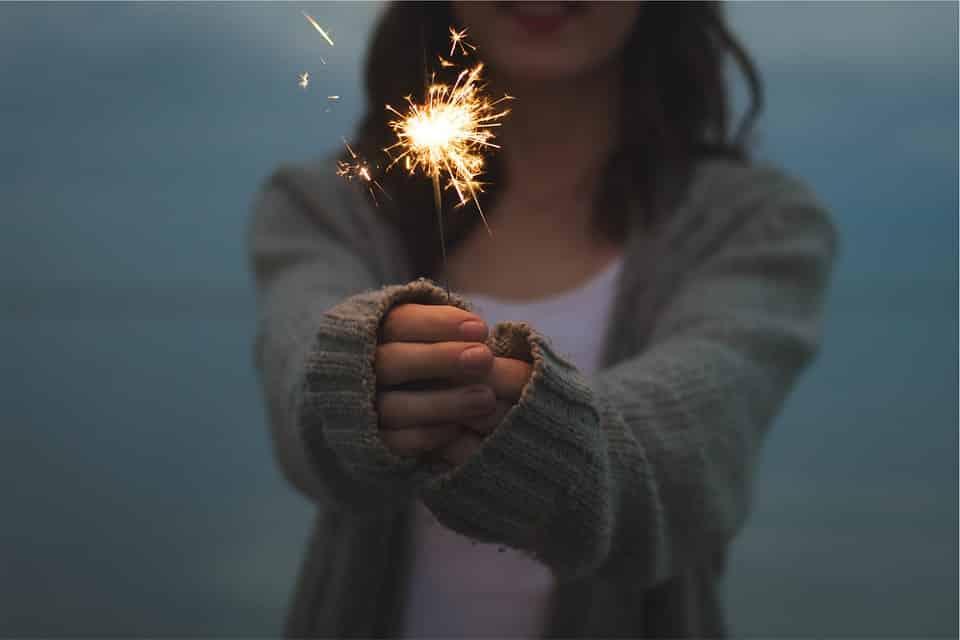 בחורה צעירה מחזיקה זיקוק די נור דולק