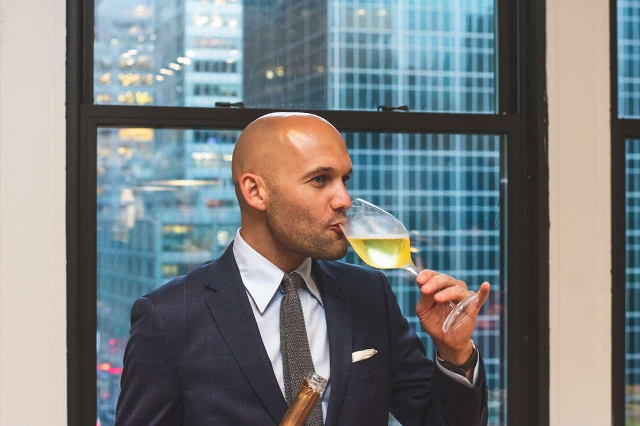 גבר עשיר קרח בחליפה שותה יין מעשן סיגר