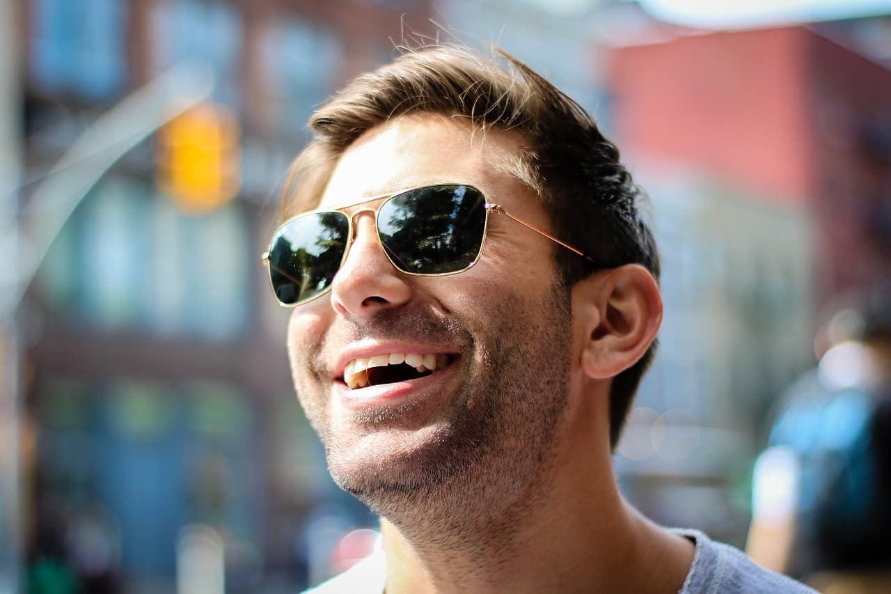 גבר צעיר עם משקפיים מחייך חיוך גדול