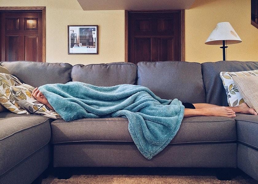 אדם שוכב על הספה ומתכסה בשמיכה כחולה
