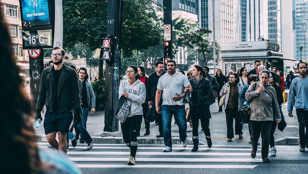 אנשים הולכים ברחוב ועוברים במעבר חצייה