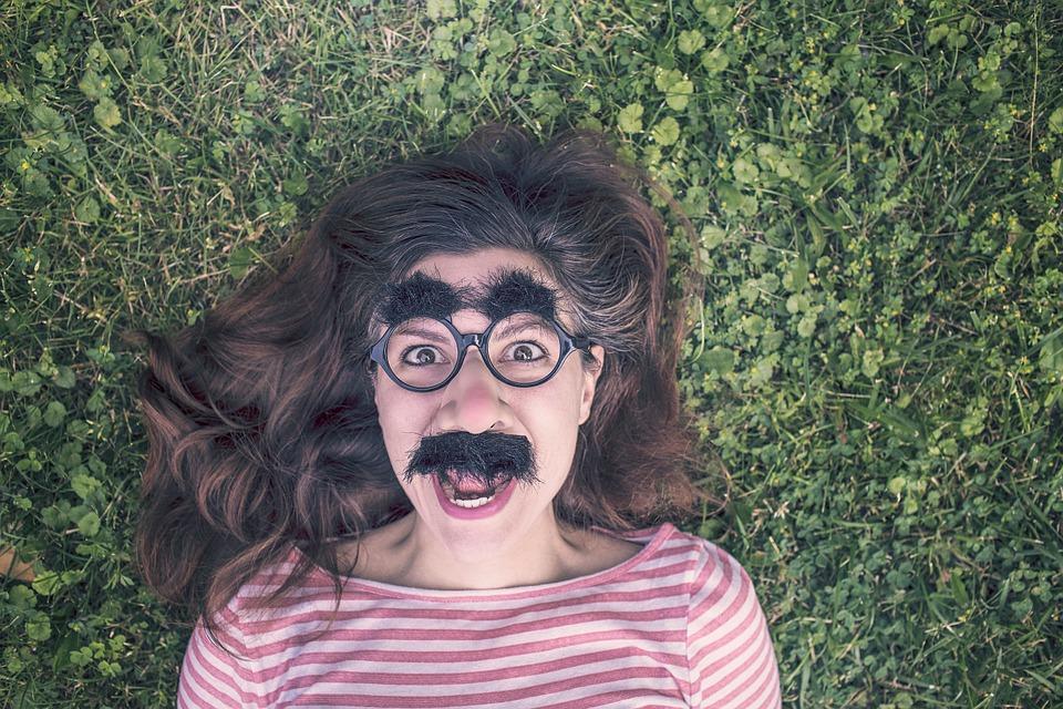 בחורה צעירה שוכבת על הדשא עם מסיכה של שפם