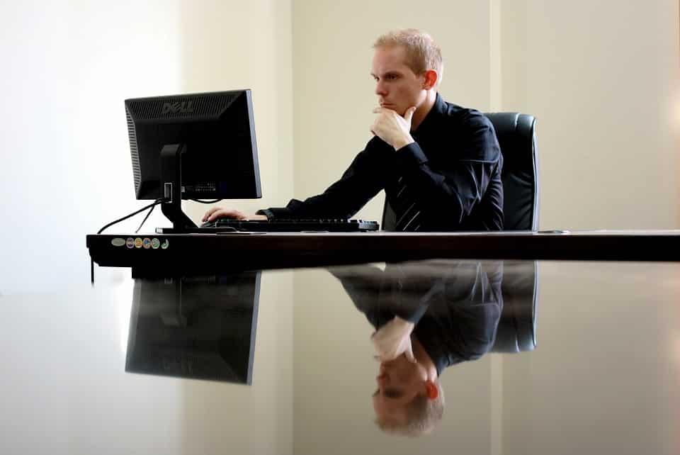 גבר יושב במשרד וכותב סיכום על רופא מומחה לנשירת שיער