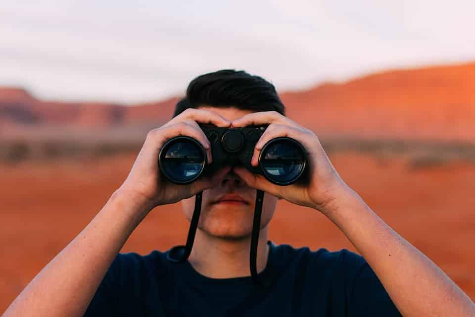 גבר צעיר צופה דרך משקפת באמצע המדבר
