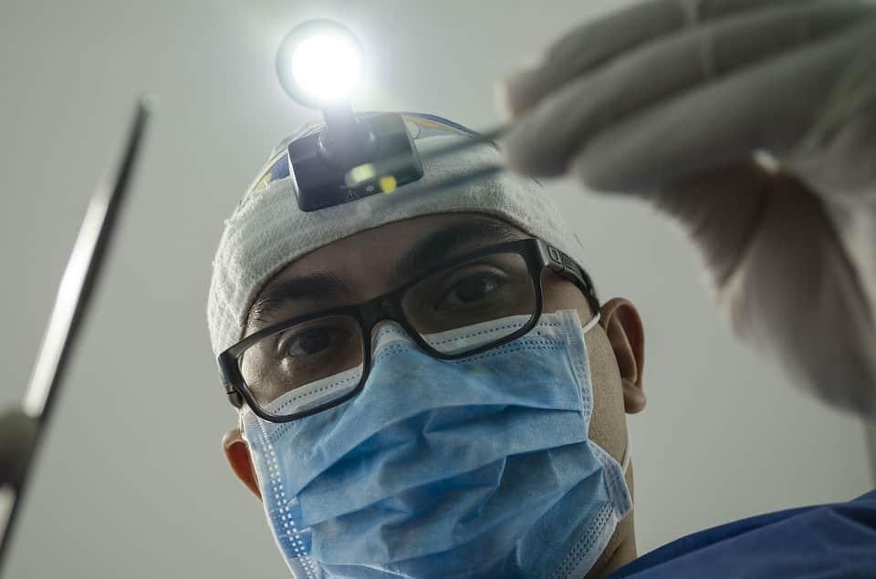 רופא מומחה להשתלות שיער בודק את המטופל מקרוב