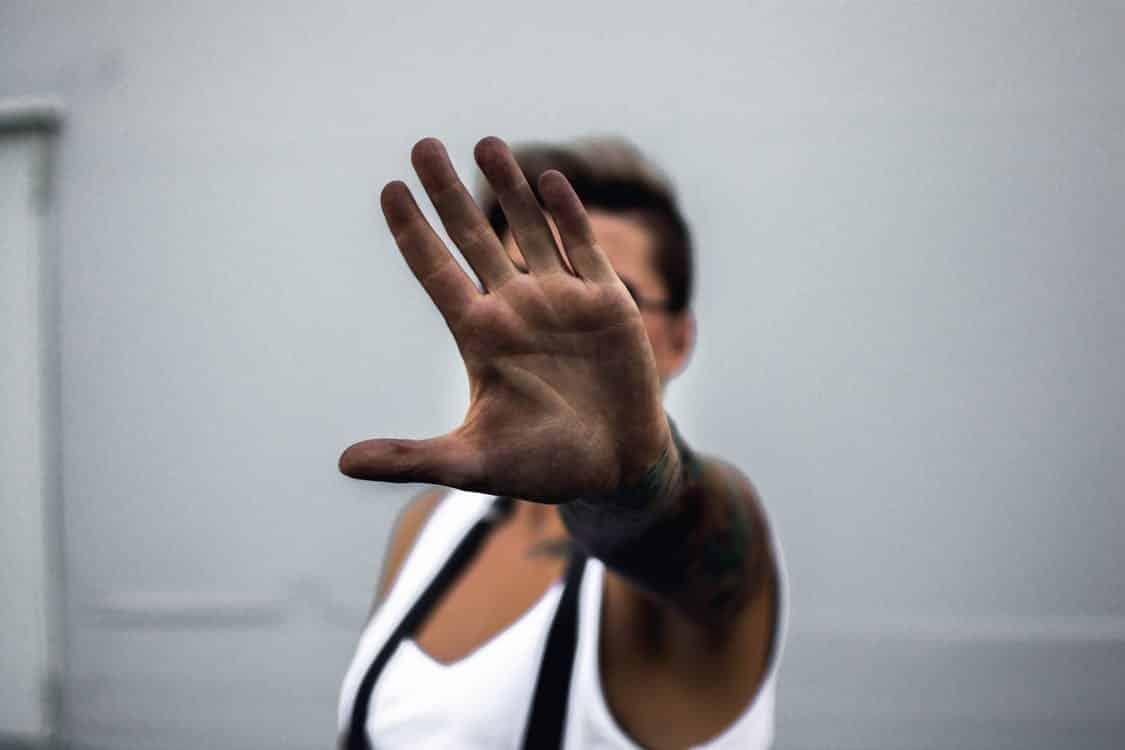 אישה שעושה תנועת עצור עם יד פתוחה