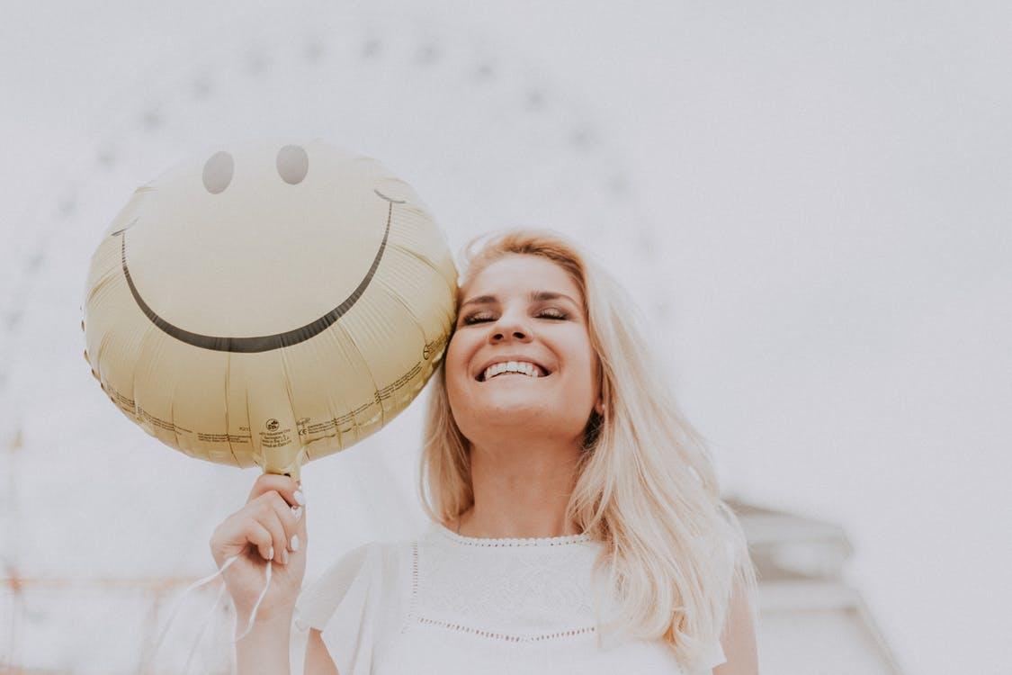 בחורה צעירה מחזיקה בלון שמצויין עליו סמיילי מחייך