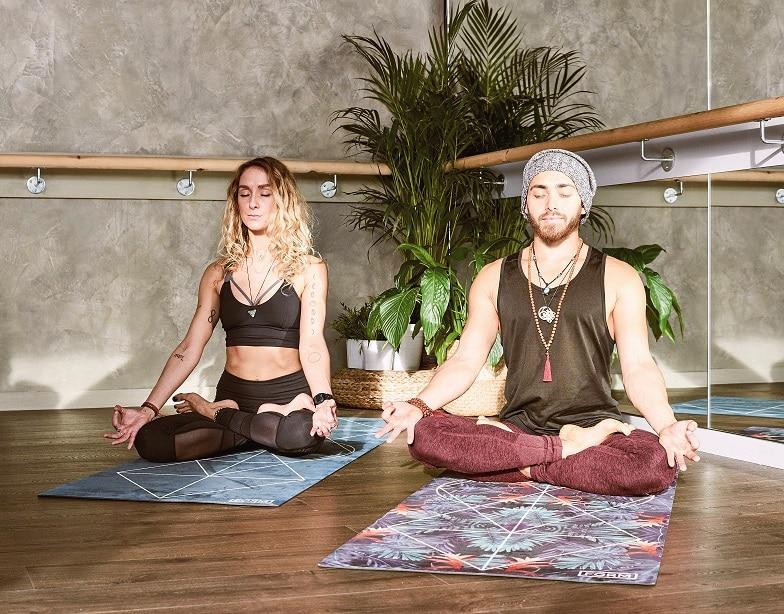 גבר ואישה עושים מדיטציה על מזרון בתוך חדר