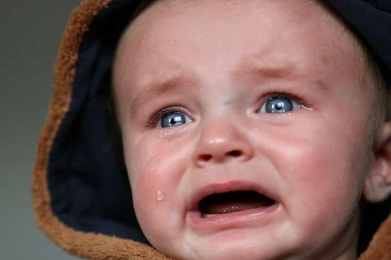 תינוק עם עיניים כחולות וקפוצו'ן בוכה