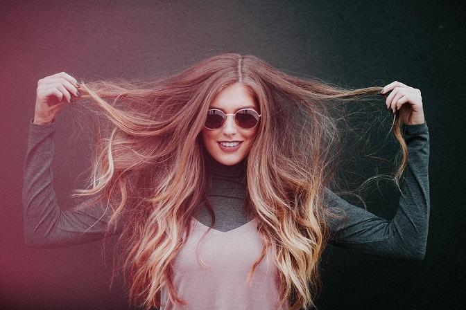 אישה צעירה עם שיער שופע מחזיקה אותו בין הידיים