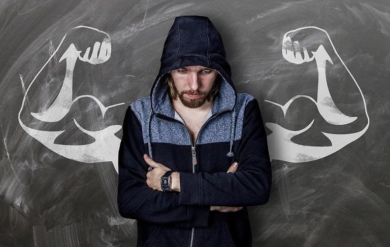 גבר בקפוצ'ון עומד על רקע של קיר שמצויירות עליו ידיים שריריות